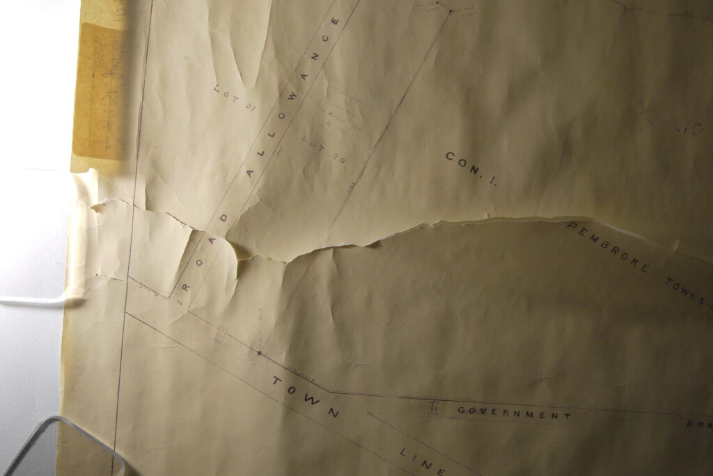 Detail of rolled and torn map before conservation treatment