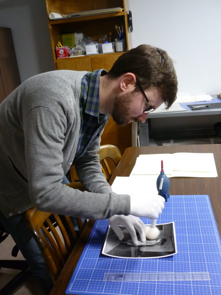 Student cleaning photographs